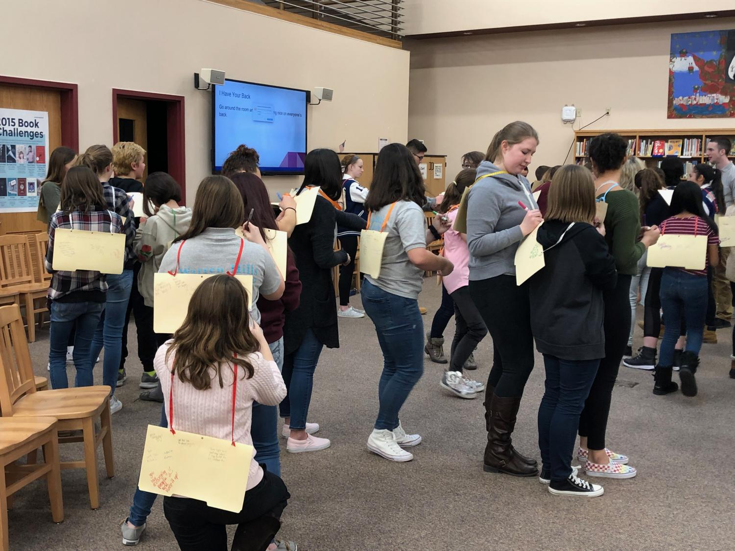 "The last activity of the day was called, ""I Have Your Back."" Pieces of thick folder covers were hung on everyone's backs. Everyone went around giving compliments and writing down only nice things. (Photo courtesy of Penny Giamoni)"