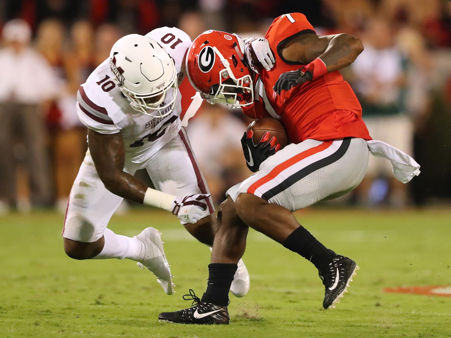 Leo Lewis, a Mississippi State football player who was the key informant in the Ole Miss-Mississippi State scandal, tackles Georgia running back D'Andre Swift in September 2017 amidst the peak of the case.  (Photo Courtesy of Curtis Compton/Atlanta Journal-Constitution/TNS)