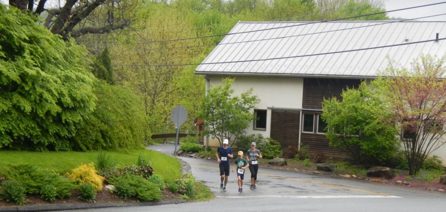 Maria Naccarato and husband Adam Duckworth and son Sebastian Duckworth run past the Musconetcong Watershed Association's River Resource Center on Maple Street in Asbury. The event raised a total of $11,690, which will help to further their education and outreach programs. (Photo by Elisha Stenger)