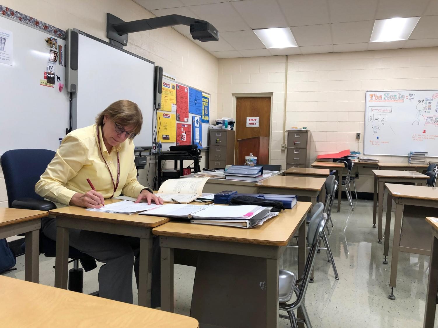 Business Technology teacher Sharyn Setzer grades assignments at her desk at the high school. The Board of Education voted Sept. 24 to change the school district's grading policy.