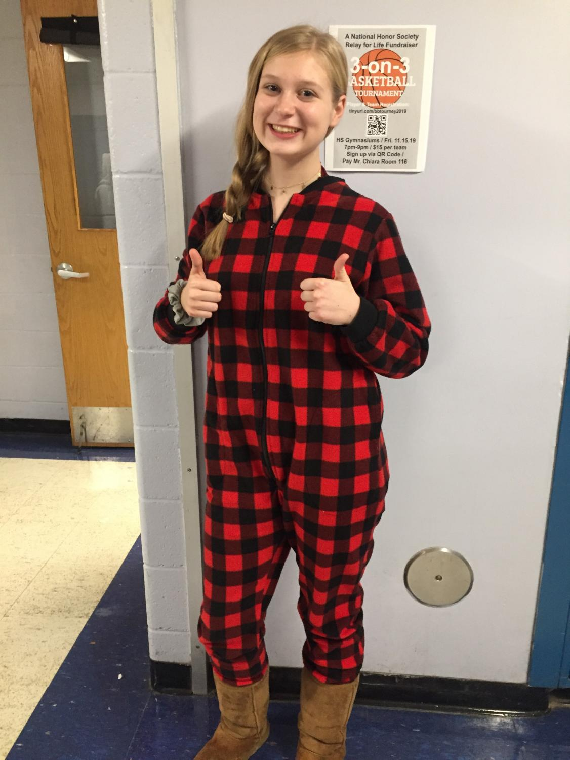 """Junior Emily Kovacsy offers two thumbs-up in favor of wearing pajamas to school in support of the recent DECA Good Grief fundraiser. Students and staff members paid $1 to wear either pajamas, a hat or blue jeans to school on Tuesday, Nov 5. Good Grief is a New Jersey Statewide Community Service Project meant to teach students """"business skills, and also serve their community and society as a whole,"""" according to the New Jersey DECA website. The proceeds from this fundraiser go to Good Grief, which provides a variety of free support for those who have lost loved ones. The Warren Hills event raised $312. Students in English Teacher Emily Kablis' homeroom were recognized for recording the highest participation rate on Good Grief day. (Photo by Samantha Lewis)"""
