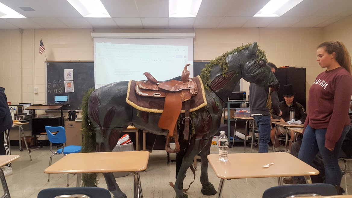 For English Teacher Emily Kablis' public speaking class this year, students were assigned to write and present a How-To Speech. For Sarah Chaplain, this meant bringing in her life-size horse statue to show her classmates how to tack up Western style. Chaplain and her father built the lifelike model along with three others, all of which are built to size. Each of her horses was designed with a certain magical creature in mind. The one she brought to class was a Threstral, but back at home, she also has a unicorn, Pegasus and water kelpie. Chaplain has been riding for practically her entire life, and she has her own, living horse, as well. Her father, an elevator mechanic, added features such as glowing eyes, moving heads, and flapping wings. It's no wonder that Chaplain got an A on her speech. (Photo by Sarah Hale)
