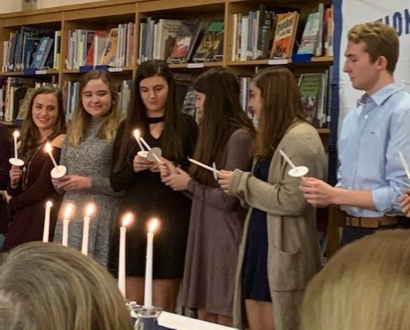 "In mid-November, the National Honor Society held their fall induction in the library for ten Class of 2020 students. The new inductees were Alyssa Cupo, Marissa Dillon, Phoenix Dougherty, Rachel Fitz, Eric Hardy, Caroline Larsen, Meghan McLaren, Leila Novljakovic, Abigail Wall, and Brooke Yencha. NHS executive members President Jordan Haytaian, Vice President Paulina Georgoutsos, Secretary Phoebe Sessler, and Treasurer Elizabeth Finnegan spoke on the the pillars of NHS, service, scholarship, leadership, and character, respectively. NHS also welcomed English teacher Penny Giamoni as the keynote speaker for the evening, who delivered a crowd-pleasing speech on the pillars as a whole, in the form of a High School Musical metaphor.  Speaking after the event, NHS advisor Carmello Chiara explained that inevitably, there are students who don't make NHS the year before, which can be frustrating, and disappointing. ""What they typically do is over the summer and then into the fall they find ways to get more involved,"" he said. ""This group seems to be people who are ready and raring to go, and eager to be involved in the school."" (Photo Courtesy of Leila Novljakovic)"