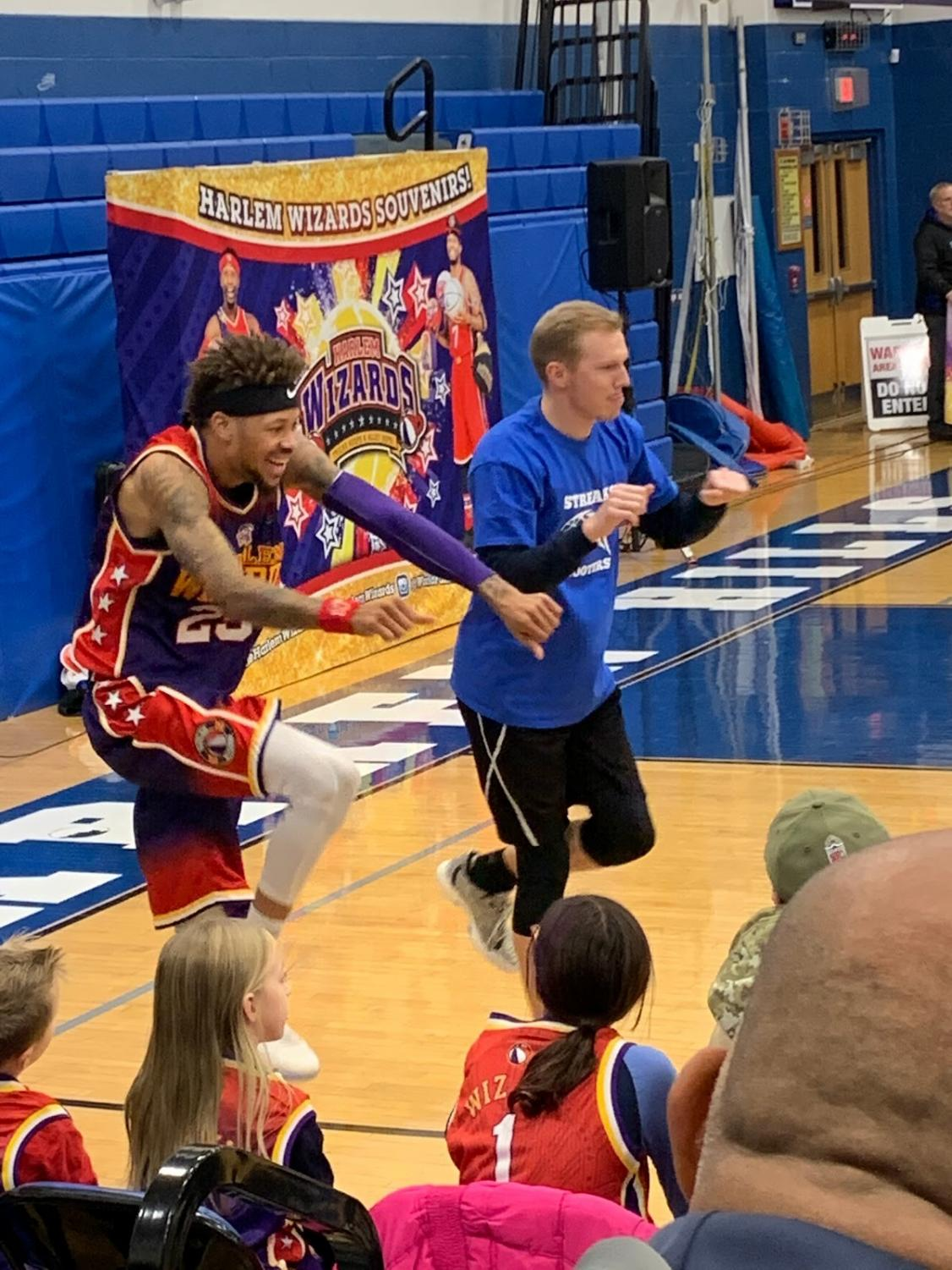 """Skywalker"" of the Harlem Wizards basketball team (left) tries out-dancing Warren Hills Varsity Basketball Coach Joseph Bamford at the high school gymnasium Dec. 7. The Warren Hills faculty took on the Wizards in a charity basketball game. The event, which was held to raise money for Project Graduation, featured basketball, dancing and other fun and games. ""It was a great way to bring the community together,"" said Sophomore Tyler Michalski, who participated in the event. (Photo by Jaedon Wolfrum)"