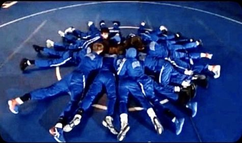 Boys wrestlers huddle to discuss strategy after doing their pre-match routine at the Hills/Hillsborough match in mid-December.  (Photo courtesy of Stephen Malia)