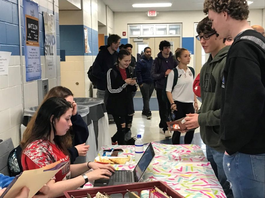 """Robert Warsen (right) purchases his Junior Prom ticket March 3 outside of the high school cafeteria. Ticket sales for prom were launched March 2, with prices starting at $75 for the first two days; on March 6, the price of each ticket will begin rising progressively, until the cost hits $90 on March 16. The Junior Prom is set for April 24 at the Eastonian Banquets and Conventions Center in Easton, Pa. This year's prom theme is """"Under the Stars."""" More information can be found on the Junior Prom's Instagram page: @wh_junior_prom. """"I'm so excited for prom,"""" Warsen said. (Photo by Samantha Lewis)"""