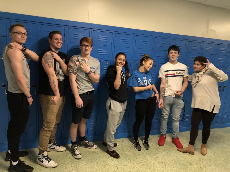 Seniors+Andrew+Reasor%2C+Austin+Domenic%2C+Nick+Hildebrant%2C+Tatiana+Santiago%2C+Sarah+Brodine+and+Bryson+Borgia+show+off+their+tattoos+with+Math+teacher+Ilona+Di+Cosmo.+%28Photo+by+Aidan+McHenry%29