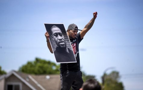 Tony L. Clark holds a photo of George Floyd outside of the Cup Foods store where he was killed while in police custody during a third day of demonstrations in Minneapolis on Thursday, May 28, 2020. (Jerry Holt/Minneapolis Star Tribune/TNS)