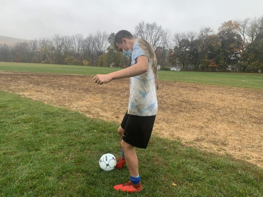 Junior soccer player Ethan Suiter wears a mask while warming up for practice.