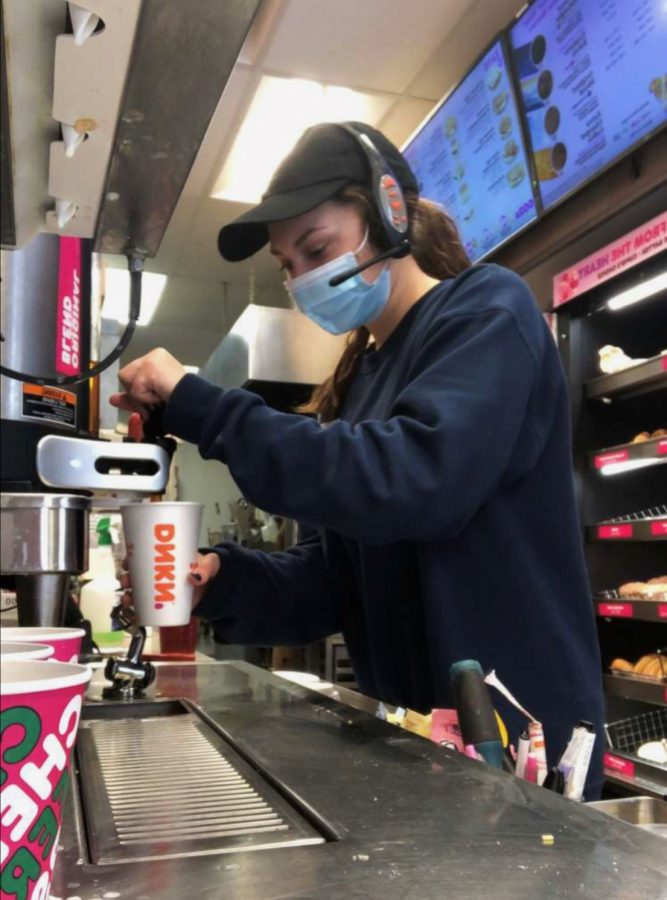 Ellie Kachala, a Warren Hills junior, prepares a customer's drink at Dunkin, where she works when she is not in school or at Swimming Team practice.