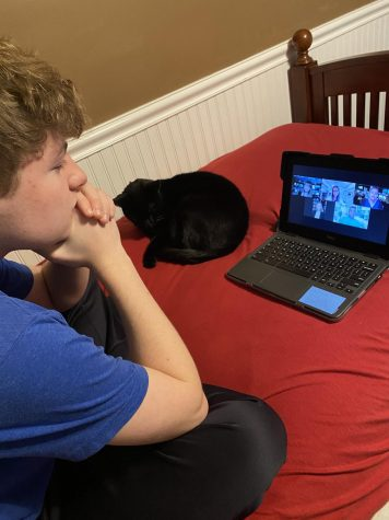 Warren Hills sophomore Ryan Cagnassola and his cat watch the Drama Club's fall play, Do You Read Me?, from the comfort of their home.