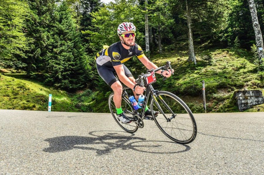 Daniel Montgomery enjoying one of his triathlon events and favorite hobbies, cycling, with a big smile on his face.